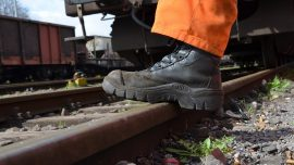 railroad track contractor with his boot on the railroad tracks